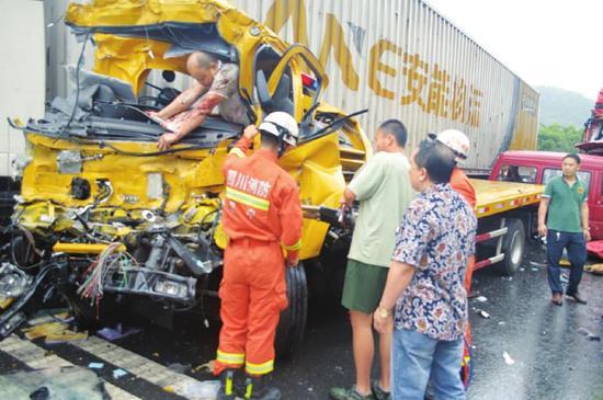 消防队员正在用破拆工具营救被卡的驾驶员。周洪攀摄