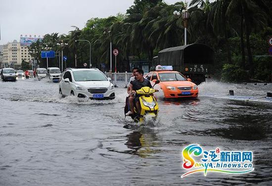 6月23日,车辆从三亚榆亚路积水路段通过。(三亚新闻网记者沙晓峰摄)