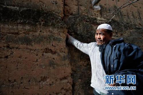 甘肃省东乡县柳树乡红庄村,村民马他非勒将手伸进已经裂缝的墙体,因为没有钱整修,一家人至今住在危房里(3月15日摄)。 新华社记者 陈斌 摄