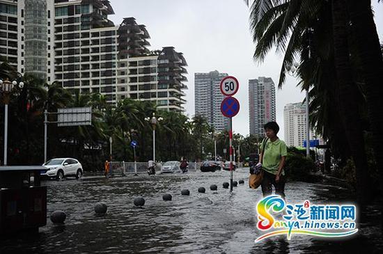 6月23日,行人从三亚榆亚路积水路段通过。(三亚新闻网记者沙晓峰摄)