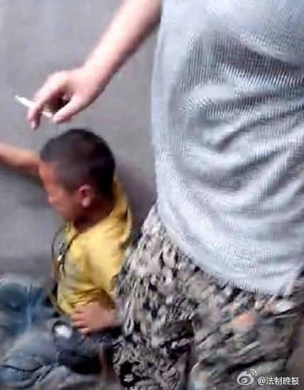 视频显示,该小学生遭到初中生暴力殴打。一初中生手持烟头,脚踩男童头部。 视频截图