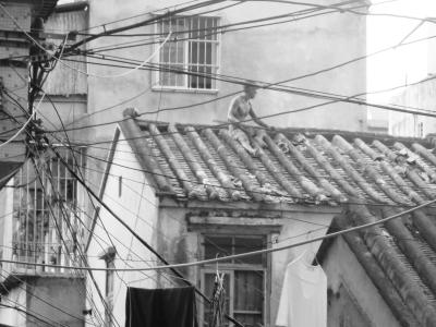 男子爬上瓦房屋顶