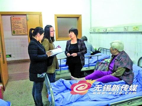 大病保险专管员在向住院病人及家属宣传大病保险政策。