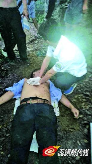 人群中,一名穿蓝色衬衫的男子倒在地上,一旁急救人员正在不停地为他按压胸口进行心肺复苏。
