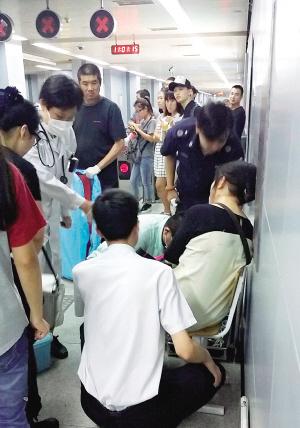 医护人员和地铁工作人员对身体不适的乘客进行检查和安抚。 本报记者 吴迪 摄