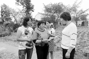 陈绍菊(左二)拿着爱心表格挨家挨户地还钱 通讯员 摄