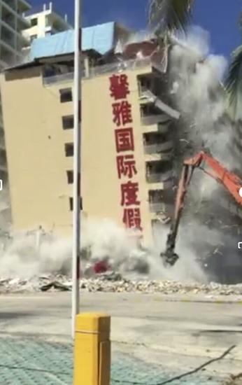 6月27日下午15点30分,馨雅国际度假酒店轰然倒地。三亚历时6天,彻底拆除这座总建筑面积达2.1万平方米的违建酒店,这是三亚迄今为止拆除单体建筑面积最大的违建酒店。(视频截图)