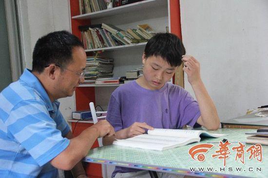 27日上午,14岁的王鑫瑞右和父亲在家查看招生手册,寻找适合报考的学校及专业