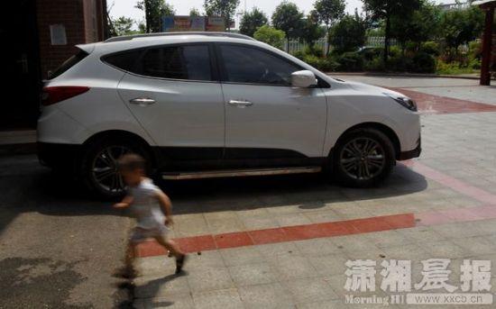 6月28日,湘潭华美丽都小区,出事的车子还停在小区里,一小朋友从车子边跑过。图/潇湘晨报记者华剑