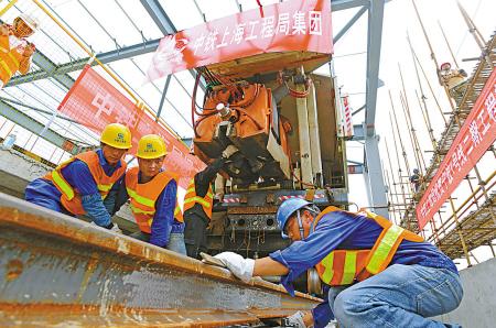 施工人员正在进行最后一处钢轨合龙接头焊接。(记者 徐能 摄)