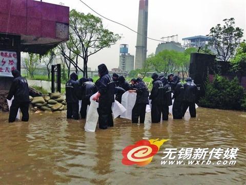 新惠路老橡胶厂被淹,城管队员在用沙袋堵漏。(李忠兰 摄)