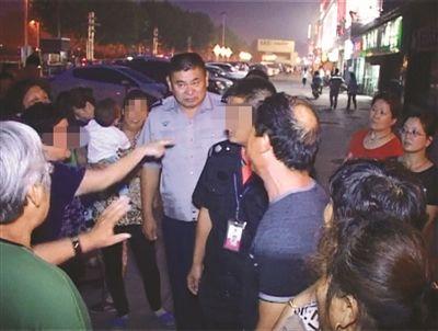 警方在协调跳舞大妈和广场保安的冲突