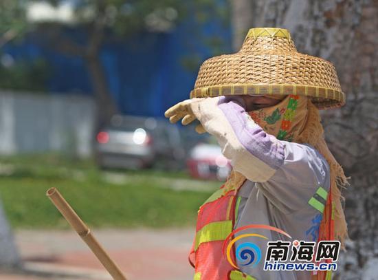 环卫工肖女士烈日下不停擦拭脸上汗水。记者汪承贤摄