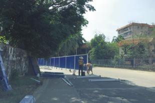 ▲工人安装围栏将道路一半封闭
