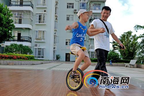 陈勋虎扶着融融,教他学习独轮车