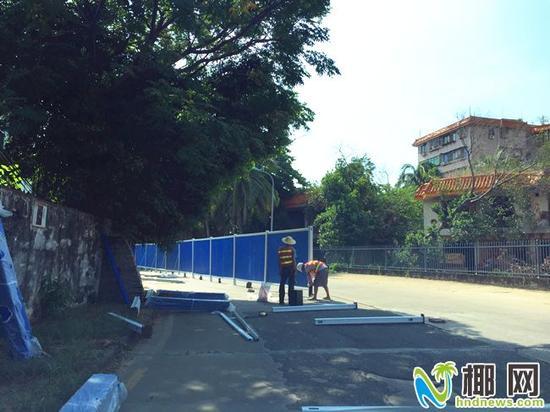 工人安装围栏将道路一半封闭