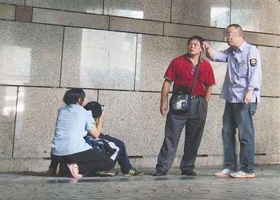 """7月4日,北京西站A1出口外,身着""""公交集团制服""""的医托与来京患者家属搭话。女家属蹲在地上,抱着生病的孩子。"""