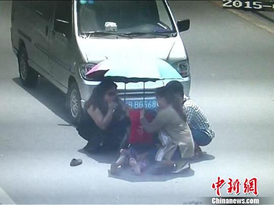 图为监控截图,两姐妹为被撞老人挡伞 交警提供 摄