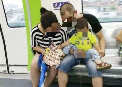 """昨天下午一点,无锡网友""""不需要太多的想法_""""在微博上发布了一张照片,照片上一对夫妇模样的男女在座位上抱着一小男孩把尿,直接便溺在车厢地面上。"""