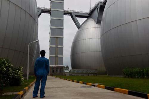 上海白龙港<a target=_blank href='http://www.liuliangji5.com'><b>污水处理</b></a>厂,一名工人走过卵形污泥消化池。寇聪汹涌材料