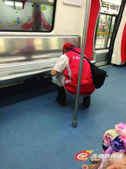 照片的主角是一位身穿红马甲、头戴志愿者帽子的老爷爷,他时而俯身擦拭地铁车厢中的坐椅,时而将捡起的垃圾放入手中的垃圾袋内。