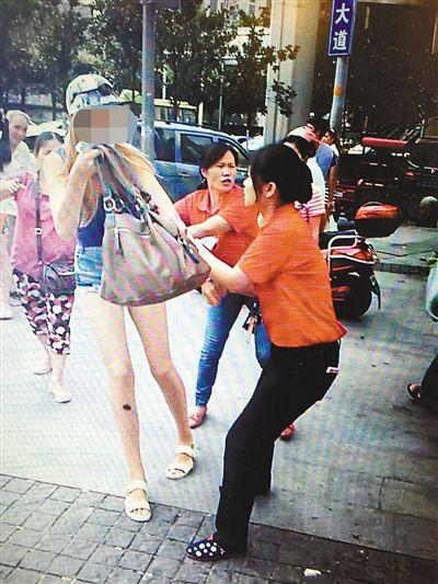 """超市员工拦住外国模特(视频截图) 被外国模特""""拿走""""的衣服"""