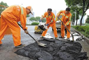昨天,鄞州区市政工作人员在鄞县大道中段用防水沥青修补道路。
