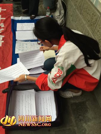 """已报考了武汉大学的树德中学高三毕业生,正在整理放在地上的""""学霸笔记"""""""
