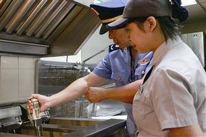 检查人员对示范早餐店炸锅里的用油情况进行检测 记者 郑晓 摄