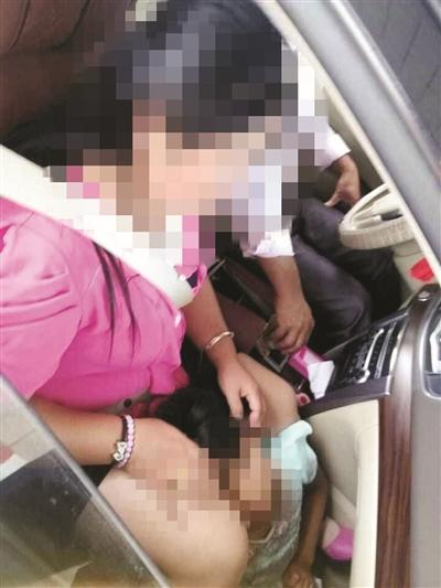 一个孩子坐在副驾驶座位下。
