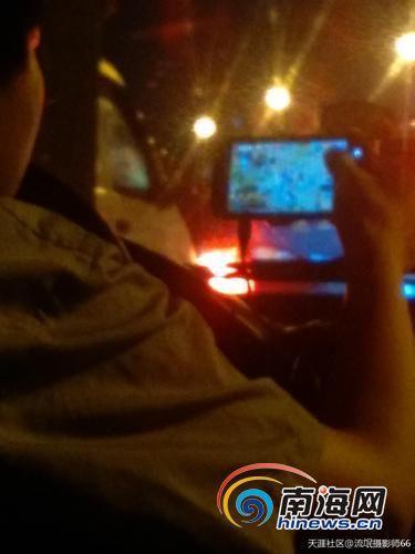 手机屏幕上依稀可见游戏画面,司机右手拇指触碰在上面。(图片来自网络)