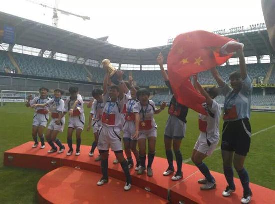 图为女足姑娘们捧起冠军奖杯