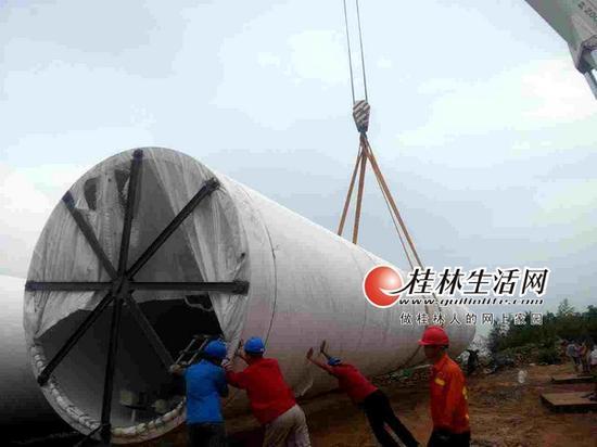 在西岭风电场9号坑位附近,重型吊机将塔筒从运输车上卸下。