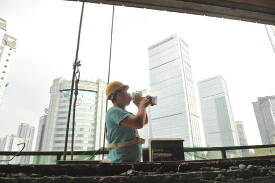 7月19日,成都市红星路二段,来自德阳的建筑工人李师傅乘坐吊篮车正在高温下作业,他每天要喝两大瓶茶水解渴。