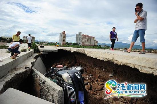 """7月21日,水中桥桥面塌陷""""吞噬""""一辆汽车引路人围观。(三亚新闻网记者沙晓峰摄)"""
