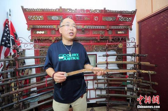 """7月20日,""""武漢抗戰文物收藏第一人""""的武漢收藏家許一兵在整理文物藏品。"""