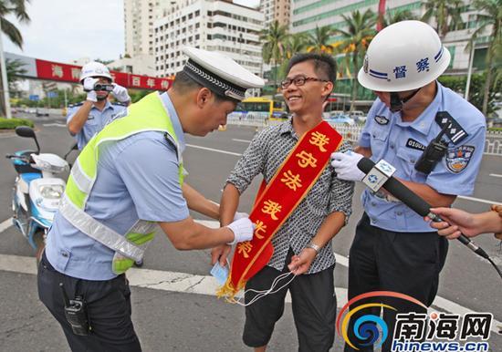 电动车主违规被抓,戴着绶带协助警方抓违规电动车辆。南国都市报记者汪承贤摄