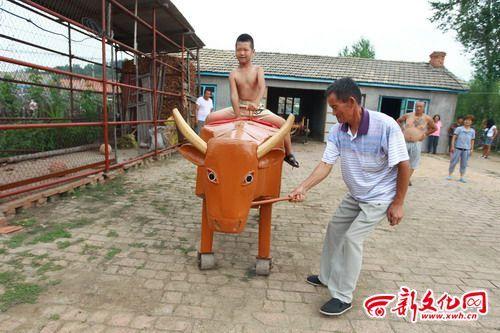 电动牛驮着小孩走来走去 新文化报 王强 摄