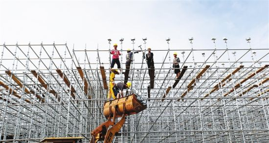 近日,海口市海秀快速干道秀英段工地,工人在加紧搭建手脚架。 张茂 摄