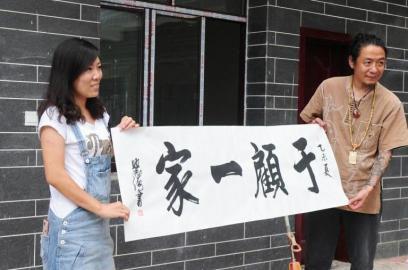 顾少强和于夫向记者展示朋友赠送的写了客栈名字的条幅。