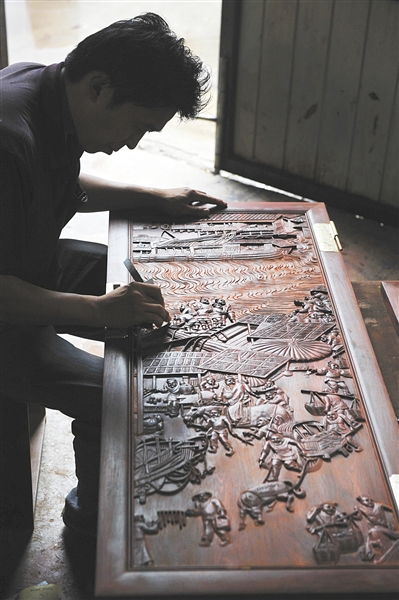 """大红酸枝最初以""""喜庆""""的色泽受到民间的垂青,后以细腻适合雕刻的特点,成为不可或缺的家居陈设。新京报记者 李飞 摄"""