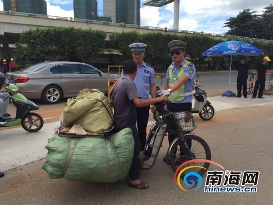 7月30日上午,民警在海口南大桥下南沙路口查处超载电动车(南海网记者组摄)