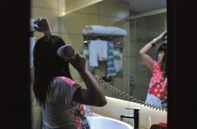 深圳一家宾馆内,很久都没能洗澡的思思终于洗了个热水澡,放松地为自己吹干头发。