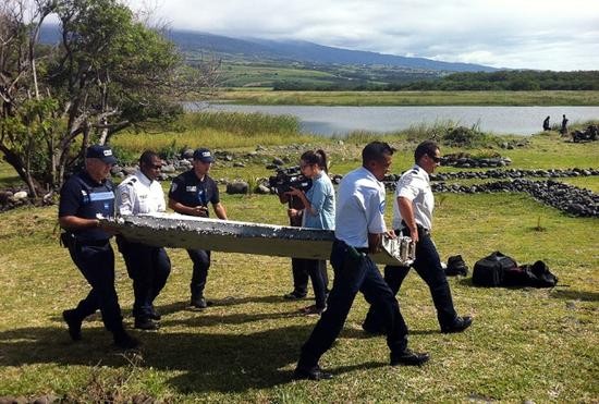 7月29日,法属留尼汪岛,警察正抬走海岸边发现的意思马航370航班机翼残块