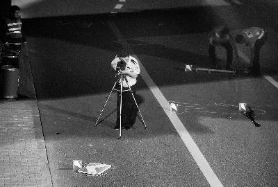图为昨晚,警方在西直门桥下勘察,标出男子坠亡的位置画圈处 摄/记者 杨益