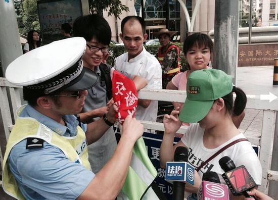 深圳市民闯红灯被罚戴绿帽执勤