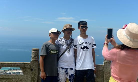 游客一家在山顶公园拍照留念