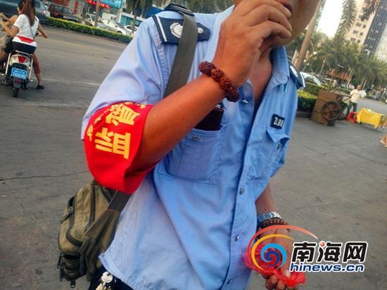 """一位""""双创""""指挥部监督员边嚼槟榔边引导车辆停在人行道上 (南海网记者刘培远摄)"""