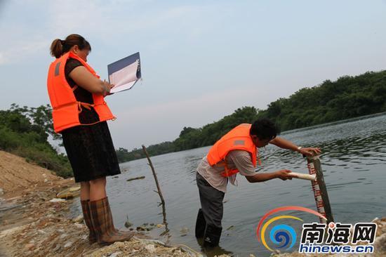庞书智和妻子李瑞兰在河边校核观测水位。省直机关工委孙勇摄