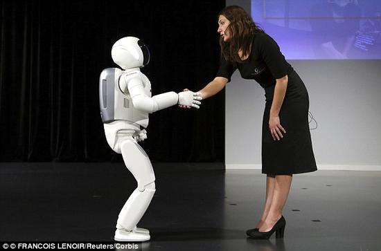 本田仿真机器人Asimo与真人握手致意。